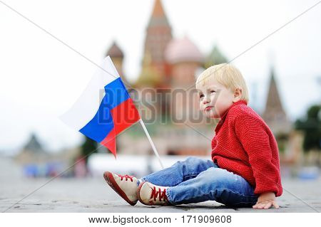 Cute Boy With Russian Flag With Red Square And Vasilevsky Descent On Background