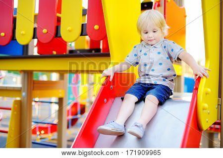 Cute Toddler Boy Having Fun On Slide On Playground