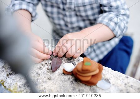 Little Boy Playing With Little Stones Outdoors