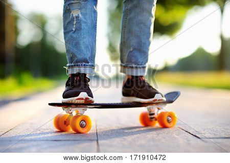 Hipster girl with skateboard outdoors. Closeup skateboarding. Active sporty woman having fun in park