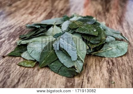 Small batch of coca leaves on wooden table, used by South Americans living in high elevations