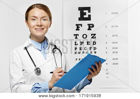 Young happy female doctor with clipboard on eyesight test chart background