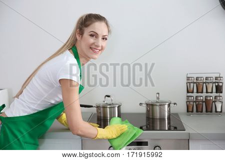 Young female worker of cleaning service working in kitchen