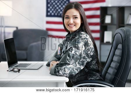 Pretty female soldier working with laptop while sitting at table in headquarters building