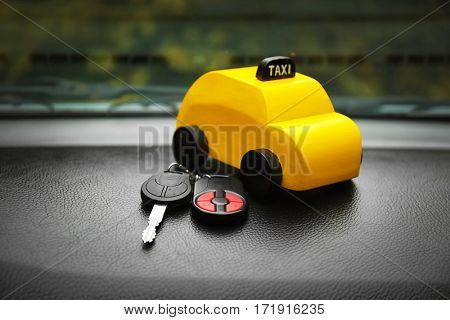 Yellow toy taxi with key on car dashboard