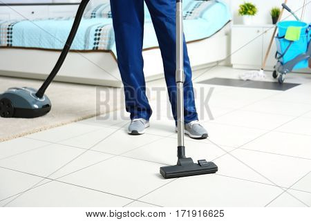 Legs of man hoovering floor with vacuum cleaner