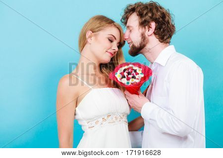 Loving couple with candy bunch bouquet flowers. Handsome man and pretty woman holding present gift. Relationship love concept.