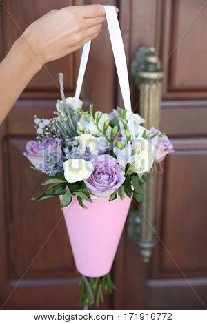 Female hand holding beautiful bouquet on door background