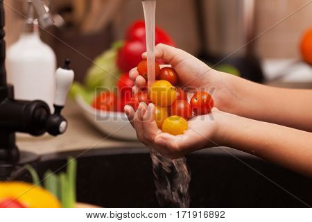 Preparing a healthy salad - child hands washing cherry tomatoes at the kitchen sink, shallow depth