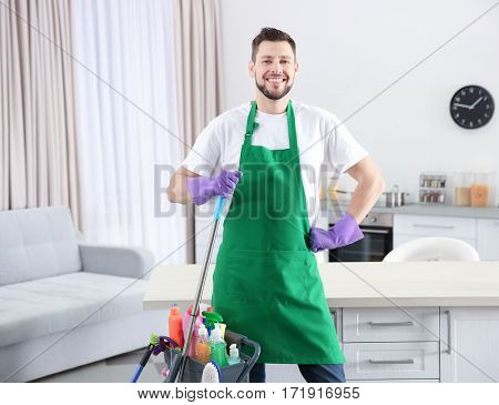 Young male worker with cleaning supplies in kitchen