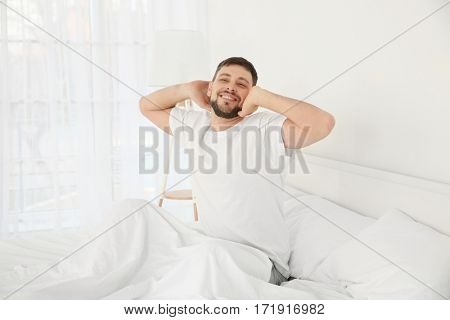 Young attractive man waking up in the morning