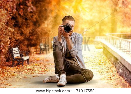 Professional photographer taking picture of beautiful autumn park