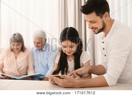 Young father and cute daughter with tablet at kitchen table