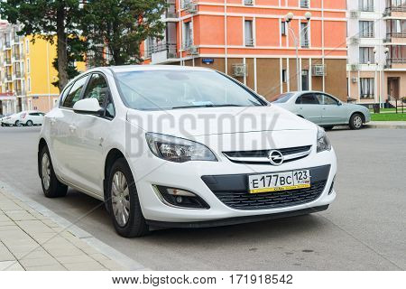 Sochi, Russia - October 11, 2016: New Opel Astra parked near modern houses in suburbia.