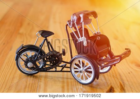 Small wooden toy three - wheeler tricycle taxi model on wooden background