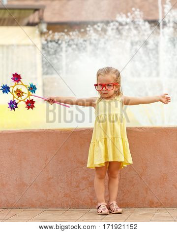 Nice little girl in glasses holds in hands of the pinwheel. A walk in the summer park near the city fountain. Summer vacation. Outdoor Activities.
