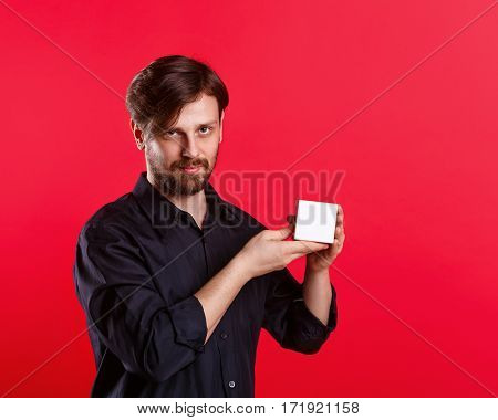 Man holding an empty cube. Advertising Space. Attractive man shows space for copy. Demonstration.