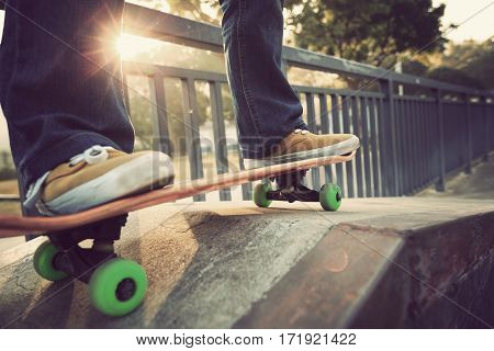 young skateboarder legs riding skateboard at skatepark ramp
