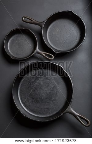 Cast iron skillet collection on black background