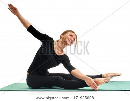 Smiling flexible woman stretching on mat before training