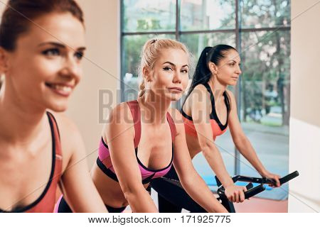 Young women exercising on stationary bicycles in fitness gym. focus on girl in the middle