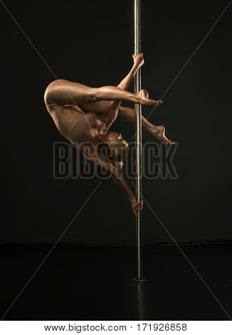 Young woman in beige lingerie with shiny gold skin posing on pylon in studio