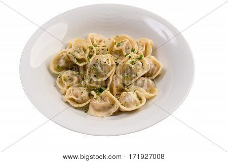 Portion of pelmeni with greenery on white plate isolated view