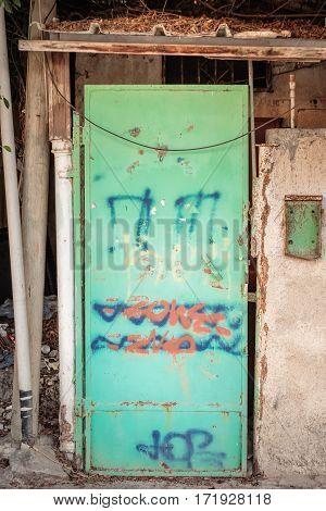 Green iron gate with graffiti in Tel Aviv, Israel.