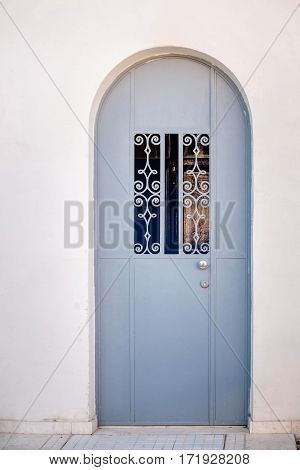 Blue iron ornamented door on white wall at sunset in Tel Aviv, Israel.