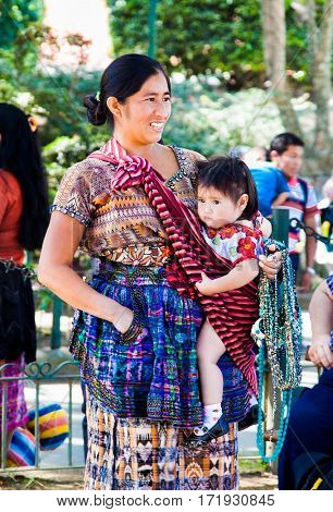 ANTIGUA,GUATEMALA -DEC 25, 2015: Guatamalian woman with baby carry at her on Dec 27, 2015 in Antigua, Guatemala.