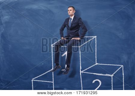 Businessman is sitting on the first place of a podium on blue blackboard background. Succes. Winning in competition. Best solutions