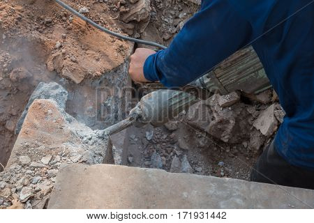 Worker Drilling Cement Concrete Floor With Machine At Construction Site