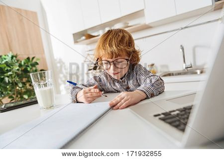 Learning new things. Nice intelligent red haired boy sitting in a sunlit room at the white table and writing something down while a glass of milk standing beside him