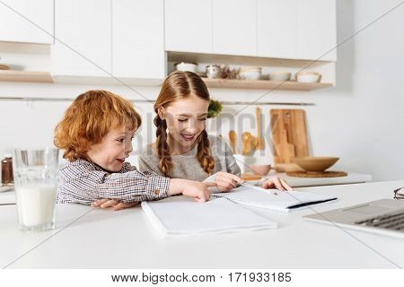 I get that. Active curious cute kid looking excited while his sister pointing at something in her notebook and they both sitting in the kitchen