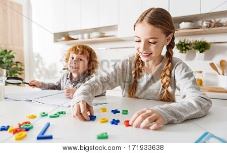 Colorful and easy. Beautiful lively positive girl sitting at the white table in a sunlit room while using some plastic numbers explaining math to her brother