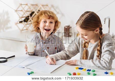 Energetic and funny. Curious positive energetic kids spending time together and looking delighted while sitting at the table