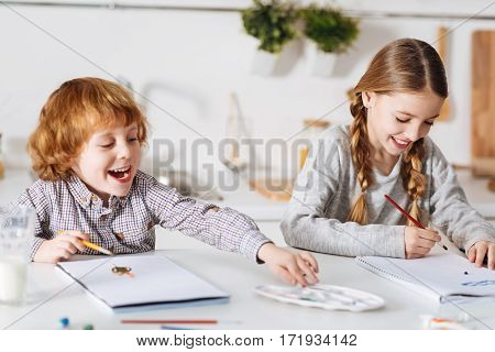 Look at that color. Adorable positive artistic siblings painting with watercolors while spending the weekend together and sitting in a roomy bright kitchen