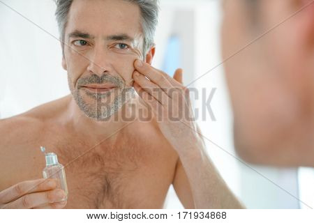 Portrait of mature man in front of mirror applying facial cream