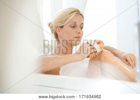 Blond woman in bathtub massaging her legs
