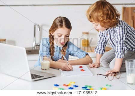 One plus one. Productive gorgeous young lady using a special game form for teaching her sibling math while spending time with him at home
