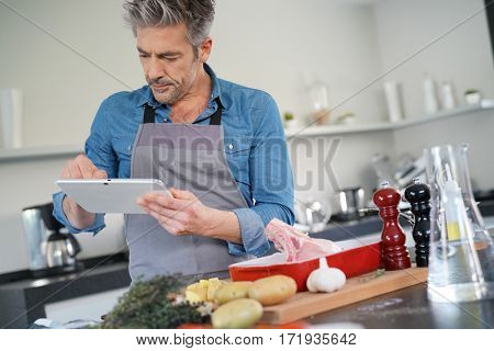Mature man in kitchen cooking with help of receipe on tablet