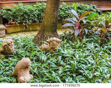 BANGKOK, THAILAND - JANUARY 17, 2014: The Jim Thompson House is the museum of Southeast Asian art. Ancient stone lions in the garden