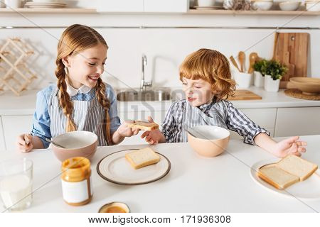 One for you. Lively caring pretty girl giving her little brother a piece of bread with peanut butter while they both sitting at the table in the morning and enjoying their breakfast together