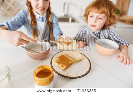 Fuel for today. Excited bright charming kids eating the first meal of the day while sitting in the kitchen before going to school