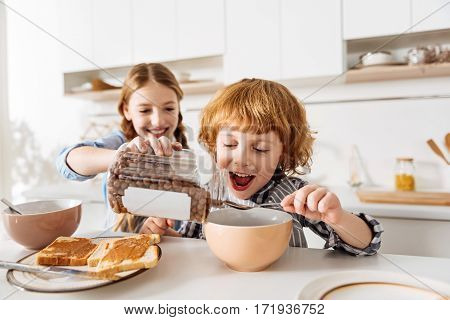 Give me more. Lively passionate cheerful kids looking excited before eating some chocolate flavored cereal while his sister pouring it in his bowl