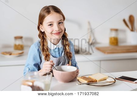 Enthusiastic start. Optimistic cute sweet child enjoying her morning meal consisting of cereal, sandwiches and milk while sitting at the table in a kitchen