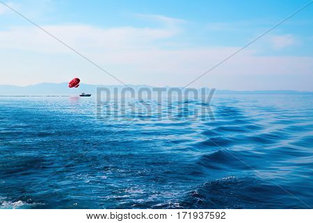 Beautiful seascape in blue colors. With red parasailer on a horizon. Cyprus