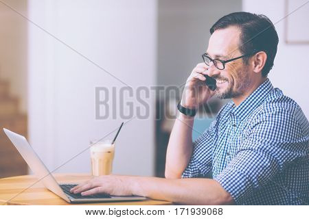 Hello. Positive smiling adult man talking on cell phone and resting in the cafe
