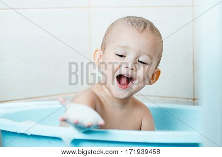 Beautiful boy bathing a toddler in the tub clean and hygieniclooks at the hand which in the foam