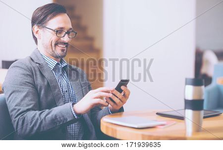 MaBrighten your life. Ceerful content bearded smiling businessman sitting at the table and using cellphone while resting in the cafe